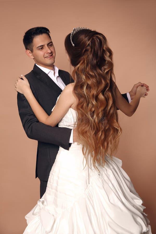 Rozochocony fornal i panna młoda dansing ślubnego tana odizolowywającego na beżu obraz stock