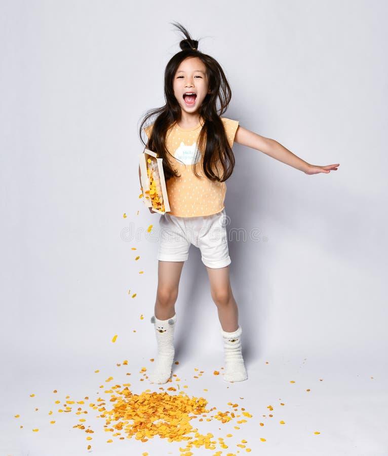 Rozochocony i aktywny azjatykci dziewczyna dzieciak w domów ubraniach zabawę w ranku śniadaniu i ignoruje jej poures za kukurydza zdjęcia royalty free