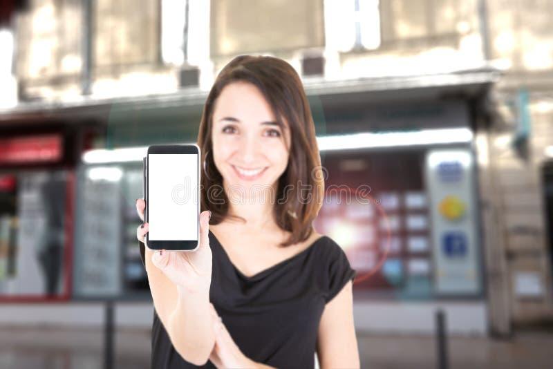 Rozochocony kobieta przód nieruchomości agencja z telefonu blanck ekranem obraz stock