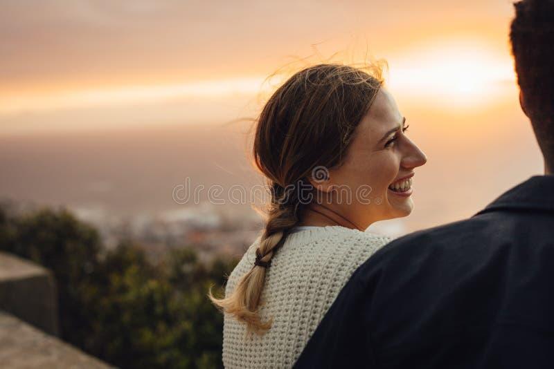Rozochocony kobiety obsiadanie z jej chłopakiem outdoors zdjęcia stock