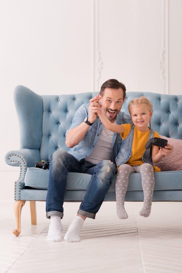 Rozochocony kochający ojciec trzyma rękę jego córka up fotografia royalty free