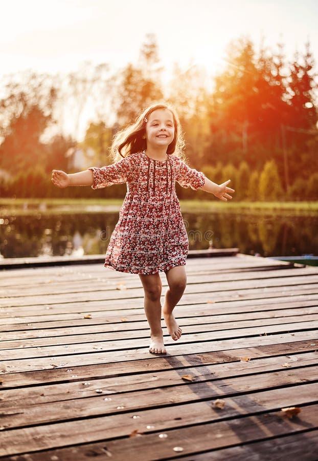 Rozochocony, littlel dziewczyna realxing na jetty obrazy stock