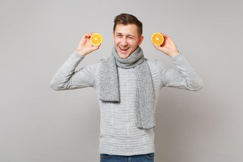 Rozochocony młody człowiek w szarym pulowerze, szalika mruganie, mienie pomarańcze odizolowywać na popielatym tle w studiu Zdrowy zdjęcie stock