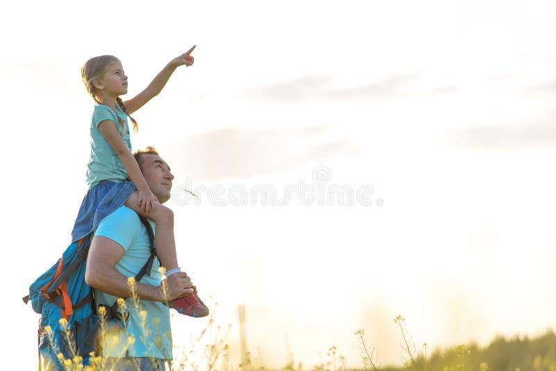 Rozochocony mężczyzna bawić się z córką na obszarze trawiastym zdjęcie stock