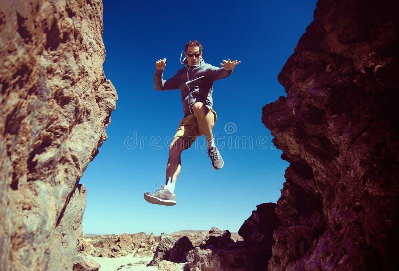 Rozochocony mężczyzna bieg na pustynnych górach obraz stock