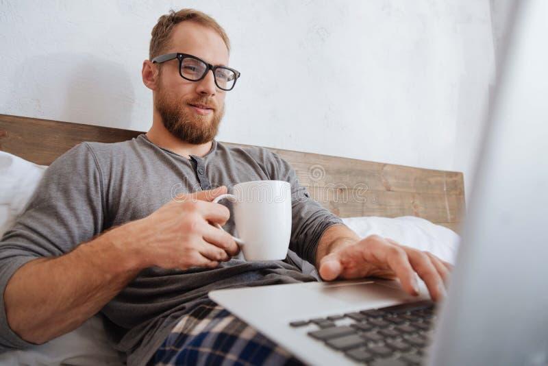Rozochocony mężczyzna pije kawę i działanie z laptopem w łóżku zdjęcie royalty free