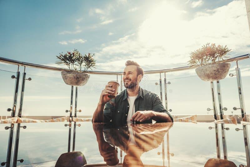 Rozochocony mężczyzna z filiżanką gorący napoju obsiadanie przy kawiarnia stołem fotografia stock