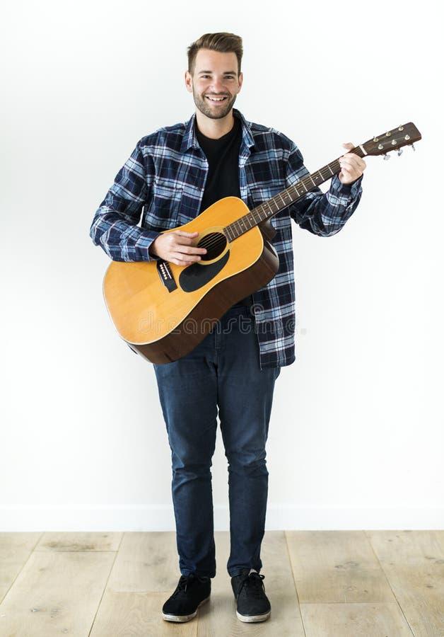 Rozochocony mężczyzna z gitarą odizolowywającą na białym tle obraz royalty free