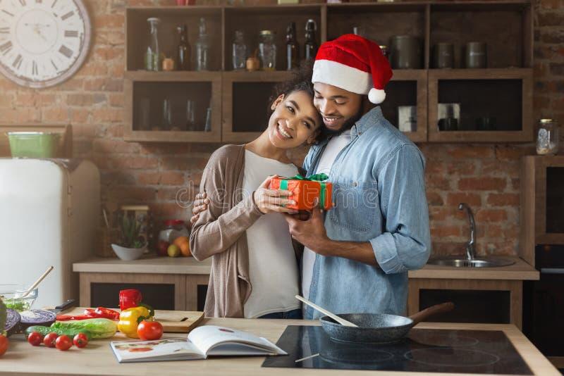 Rozochocony mężczyzna zaskakuje jego dziewczyny z Bożenarodzeniowym prezentem obraz stock