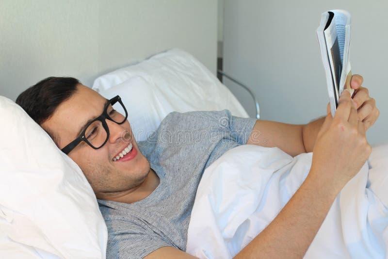 Rozochocony męski czytanie coś zabawa w łóżku obraz stock