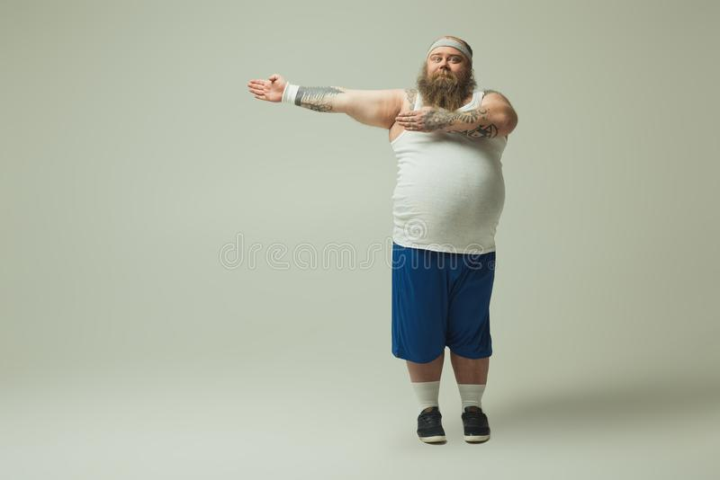 Rozochocony męski fatso wskazuje rękę z ukosa w sportswear zdjęcia royalty free