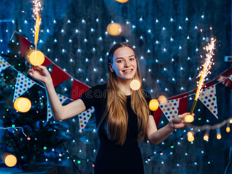 Rozochocony młodej kobiety mienia sparkler w ręce boże narodzenie nowy rok zdjęcia stock
