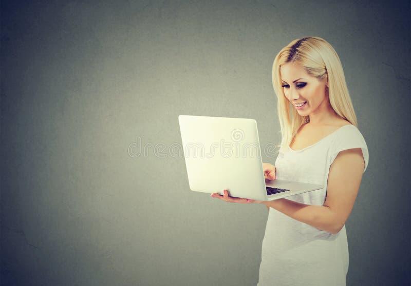 Rozochocony młodej kobiety mienie i używać laptop fotografia stock