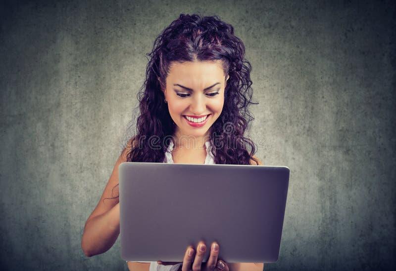 Rozochocony młodej kobiety mienie i używać laptop obraz royalty free