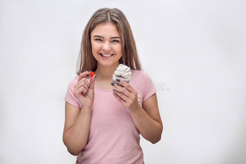 Rozochocony młodej kobiety spojrzenie na kamerze i uśmiechu Trzyma galaretowego cukierki tort i pojedynczy białe tło zdjęcia stock