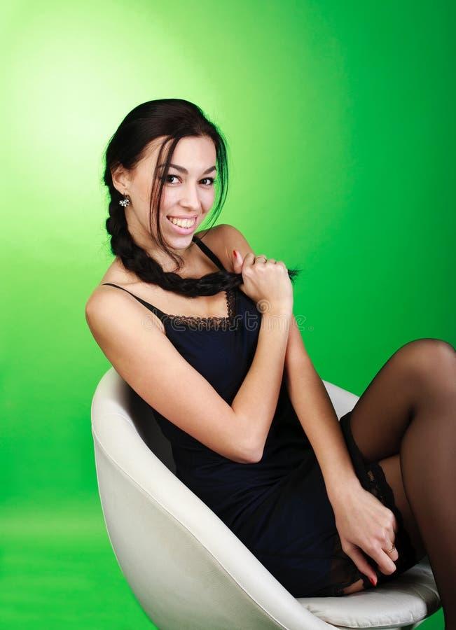 Rozochocony młody brunetki dziewczyny obsiadanie na białym krześle obrazy stock