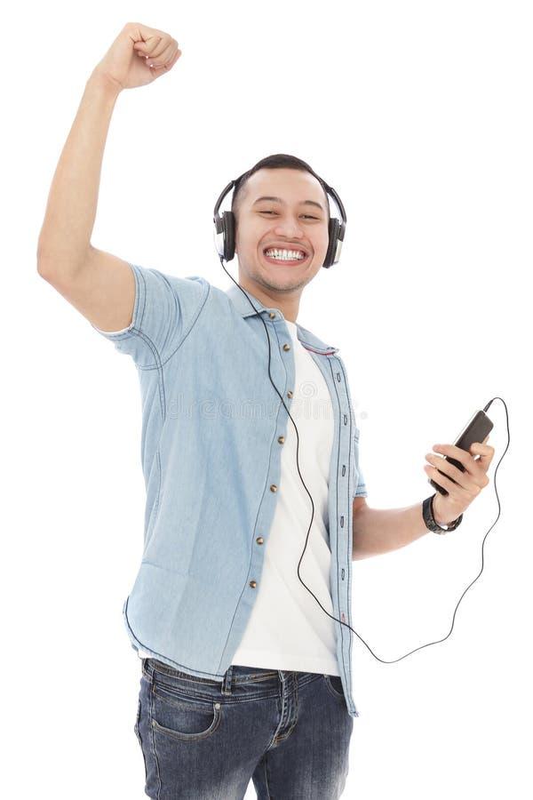 Rozochocony młody człowiek cieszy się słuchającą muzykę na telefonie komórkowym z hea zdjęcia royalty free