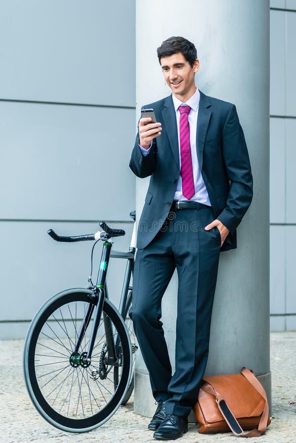 Rozochocony młody człowiek komunikuje na telefonie komórkowym podczas gdy czekający o obraz royalty free
