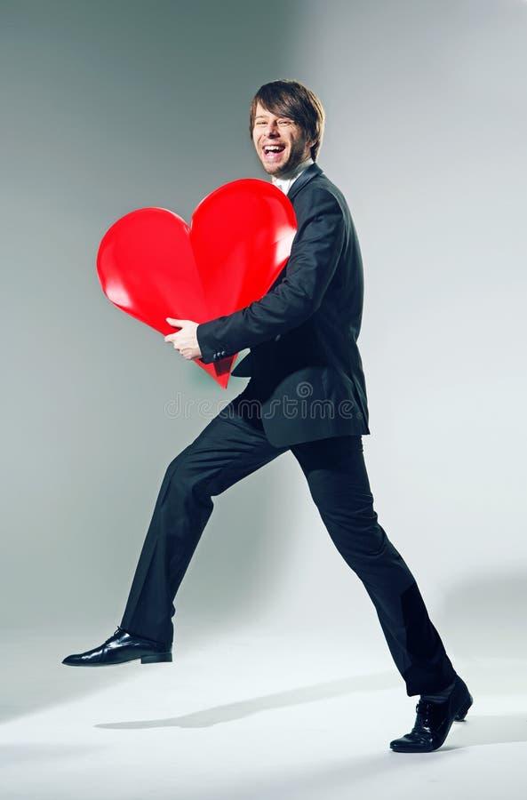 Rozochocony młody człowiek trzyma dużego serce zdjęcie stock
