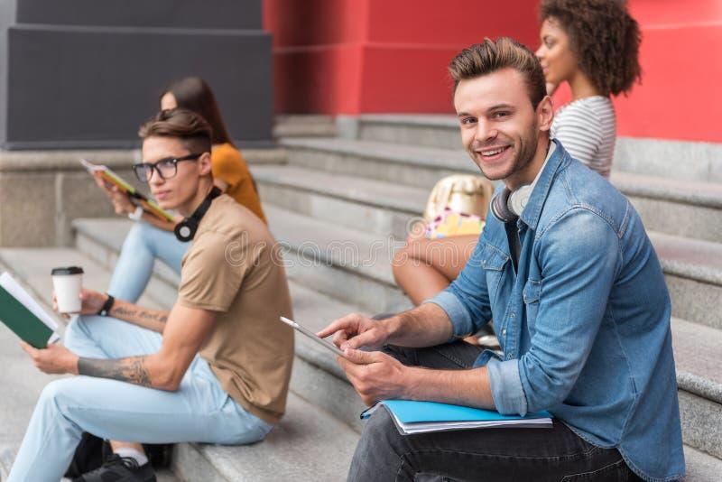 Rozochocony młody człowiek używa gadżet podczas gdy siedzący na krokach zdjęcie royalty free