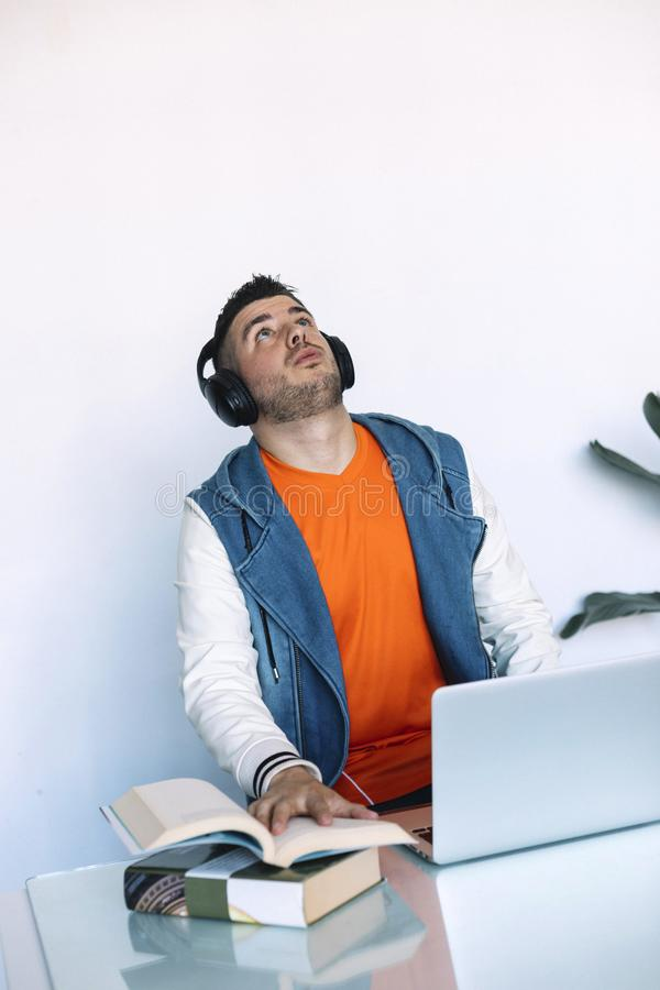 Rozochocony m?ody cz?owiek s?ucha muzyka w he?mofonach podczas gdy siedz?cy przy jego pracuj?cym miejscem obraz royalty free