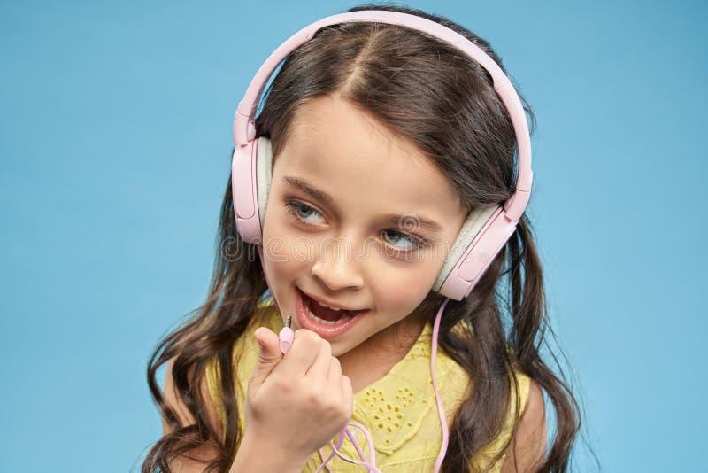 Rozochocony małej dziewczynki pozować, jest ubranym w różowych hełmofonach zdjęcia stock