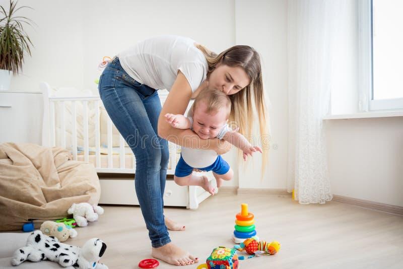 Rozochocony macierzysty bawić się z jej chłopiec przy żywym pokojem obraz royalty free