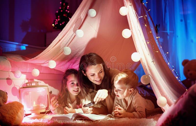 Rozochocony macierzysty czytanie powieść dla jej dzieci zdjęcie stock