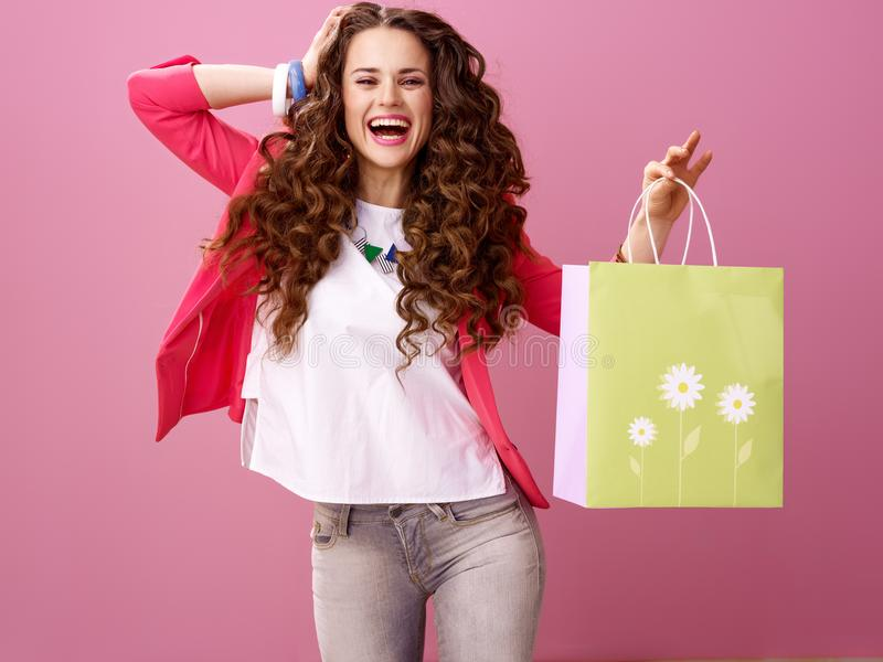 Rozochocony nowożytny kobieta kupujący odizolowywający na różowym tle zdjęcia stock