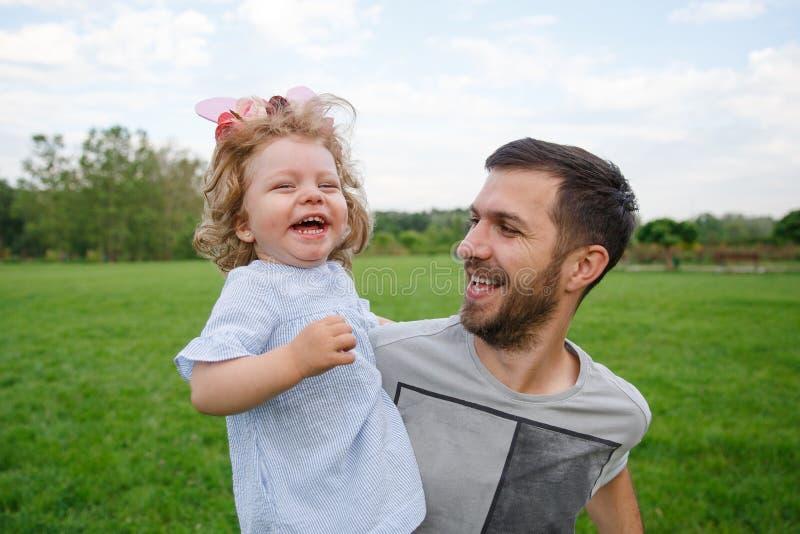 Rozochocony ojciec niesie uśmiechniętej córki w parku obraz royalty free