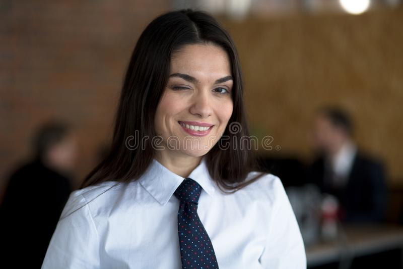 Rozochocony ono uśmiecha się mruga bizneswoman w białej bluzce i czarnym krawacie Dwa colleguaes pracują za ona zdjęcia royalty free