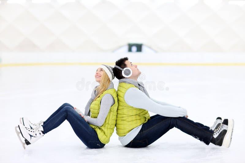 Rozochocony pary obsiadanie na łyżwiarskim lodowisku zdjęcie stock