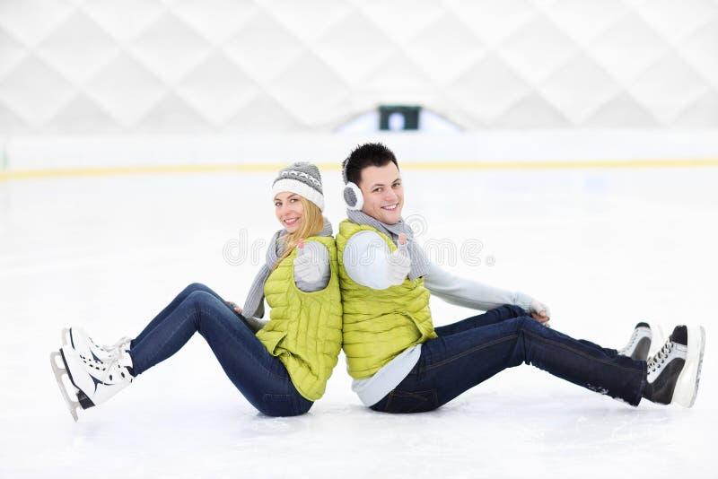 Rozochocony pary obsiadanie na łyżwiarskim lodowisku obrazy stock
