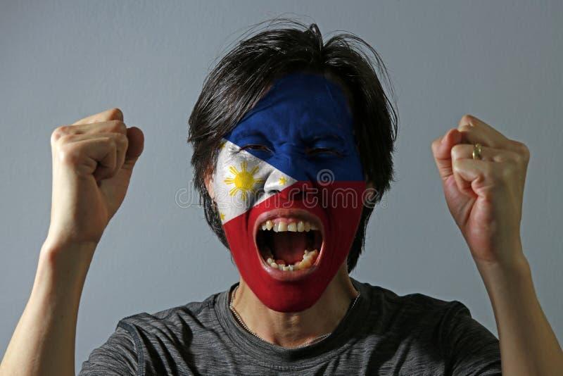 Rozochocony portret mężczyzna z flagą Filipiny malował na jego twarzy na popielatym tle obraz royalty free