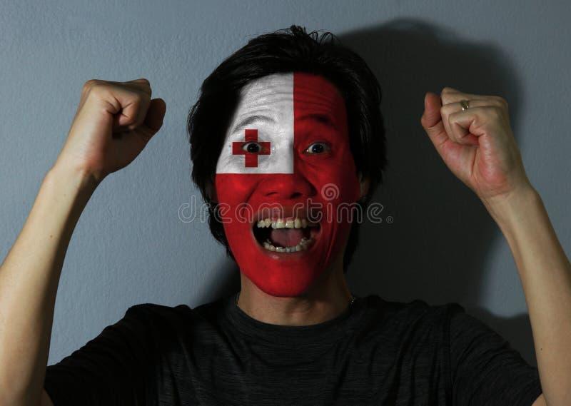 Rozochocony portret mężczyzna z flagą Tonga malował na jego twarzy na popielatym tle zdjęcia royalty free