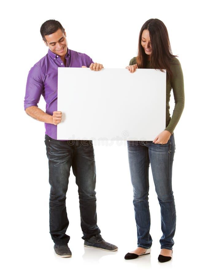 Rozochocony potomstwo pary spojrzenia puszek Przy Pustym plakatem zdjęcia stock