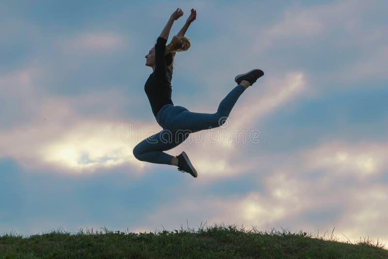 Rozochocony Pozytywny dziewczyny doskakiwanie w Lotniczych Plenerowych ranek chmurach, atlety kobieta Skacze Pięknego wschód słoń zdjęcia royalty free