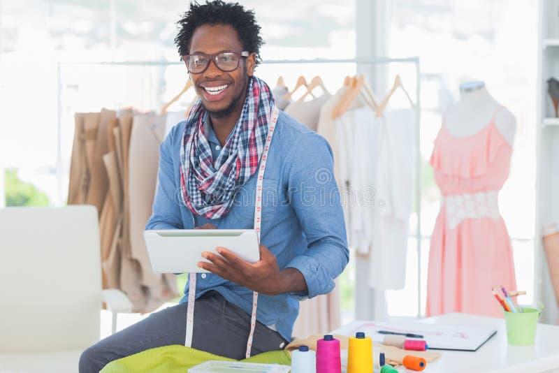 Rozochocony projektant mody trzyma cyfrową pastylkę fotografia royalty free