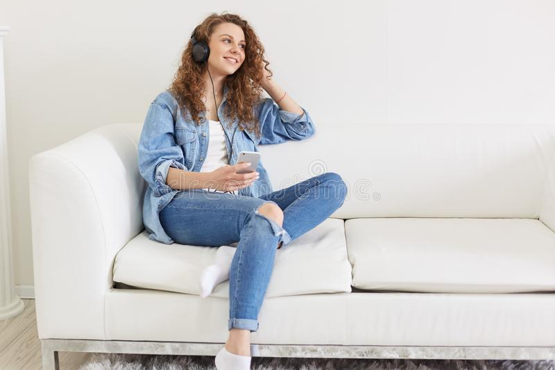 Rozochocony przyjemny żeński obsiadanie na kanapie, patrzejący na boku, trzymający jej smartphone, mieć słuchawkę, słucha ulubion zdjęcia royalty free