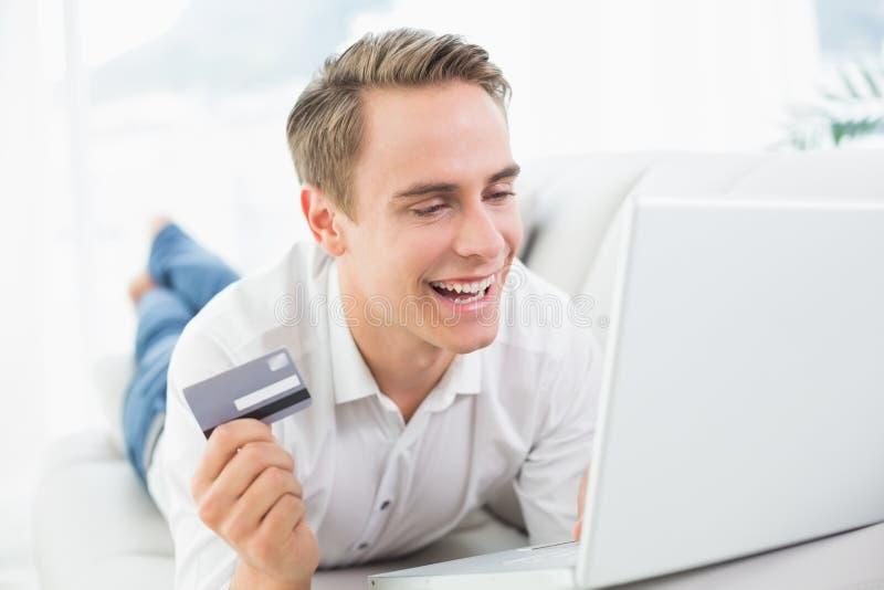 Rozochocony przypadkowy młody człowiek robi online zakupy na kanapie fotografia stock