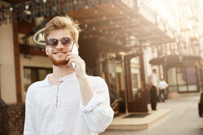 Rozochocony przystojny czerwony z włosami facet z modną fryzurą i brodą, w brandnew okularach przeciwsłonecznych opowiada na tele zdjęcie royalty free