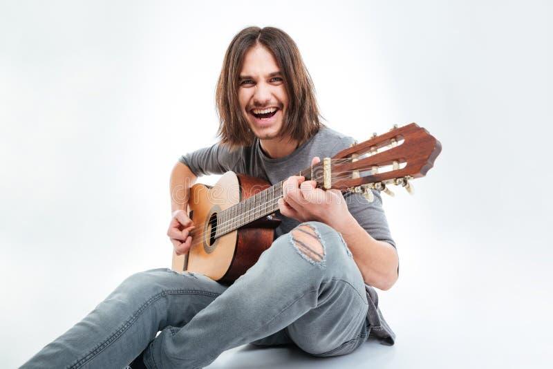 Rozochocony przystojny mężczyzna z długie włosy obsiadania i bawić się gitarą zdjęcie royalty free