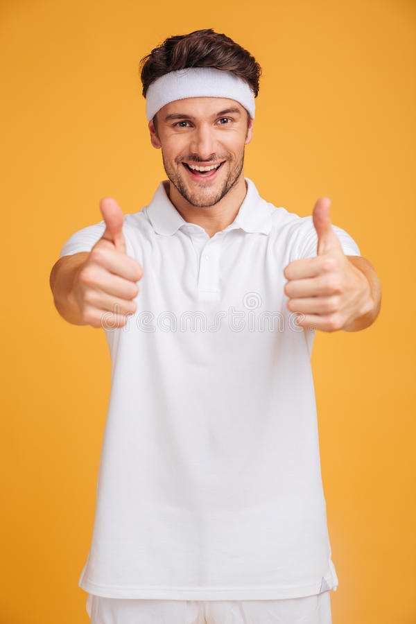 Rozochocony przystojny młody sportowiec pokazuje aprobaty z oba rękami zdjęcia royalty free