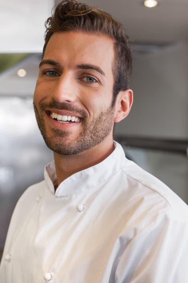 Rozochocony przystojny młody szef kuchni patrzeje kamerę obraz stock