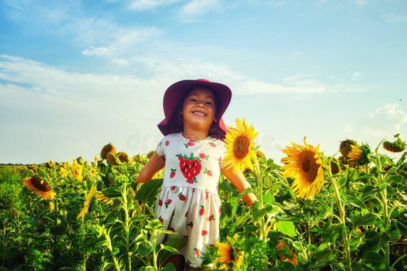 Rozochocony radosny dziecko w polu z słonecznikami zdjęcie royalty free