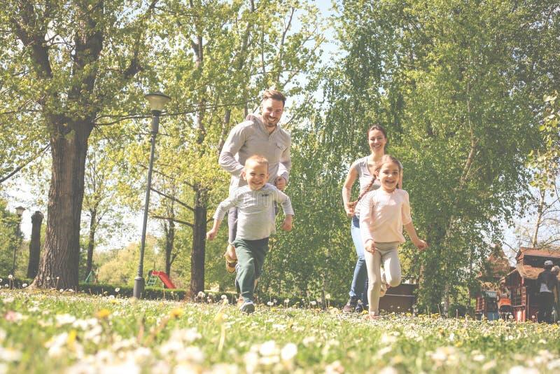 Rozochocony rodzinny bawić się z ich dziecka ` s w łące zdjęcie stock