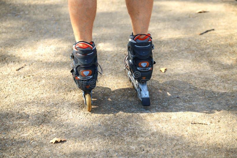 Rozochocony sporty mężczyzny 50-55 lat jedzie rolkowego łyżwiarstwo w parku w jesień sezonie, rollerblading jak zdrowego ćwiczeni obraz royalty free