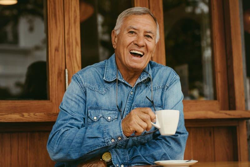 Rozochocony starszy mężczyzna ma kawę przy kawiarnią obrazy stock