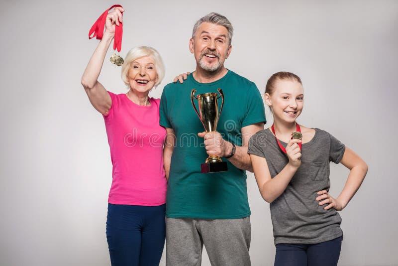 Rozochocony stary pary i dziewczyny mienie bawi się trofeum i medale obraz royalty free