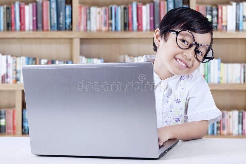 Rozochocony Studencki Używa laptop w bibliotece obraz royalty free